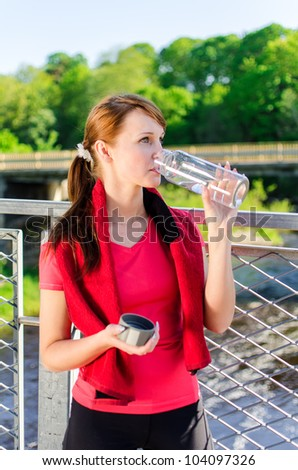 Attractive woman drinking water on the bridge