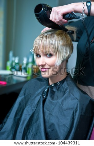 attractive woman drying her wet hair in hair salon