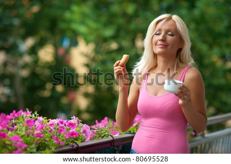 attractive woman eating breakfast on her home balcony