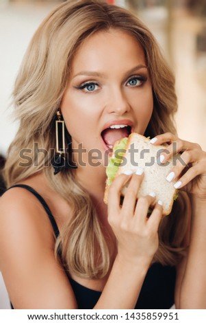 Attractive woman eating delicious sandwich in cafe #1435859951