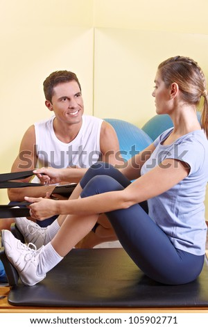 Attractive woman exercising in fitness center and talking to male fitness trainer
