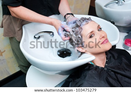 attractive woman getting her hair washed at hair salon