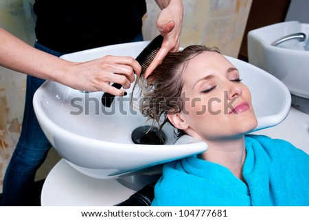 attractive woman having her hair washed in salon