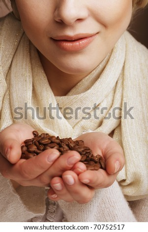 Attractive woman holding coffee beans.