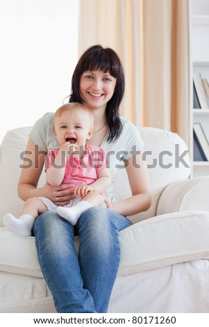 Attractive woman holding her baby in her arms while sitting on a sofa in the living room