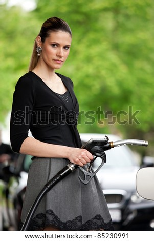 attractive woman holding nozzle at gas station