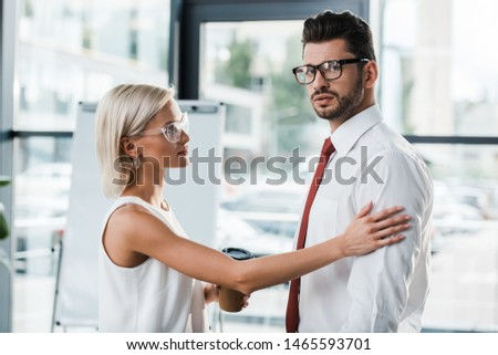 attractive woman holding paper cup and touching sad coworker in office