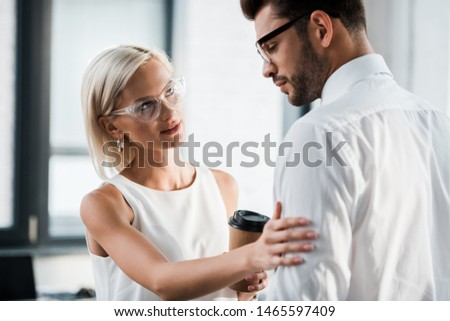 attractive woman holding paper cup and touching upset coworker in office