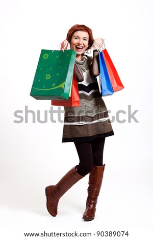 attractive woman holding shopping bags against a white background