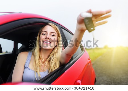 Attractive woman in a car showing keys at sunset.