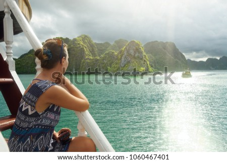 Attractive woman in a dress is traveling by boat in Halong Bay. North Vietnam.