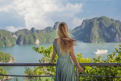 Attractive woman in a dress is traveling in Halong Bay. Vietnam. Travel to Asia, happiness emotion, summer holiday concept. Picturesque sea landscape. Ha Long Bay, Vietnam