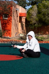 Attractive woman in a white hoodie in the playground launches quadcopter, squinting in the sun. Professional drone quadcopter with digital camera in hand. Fallen damaged quadcopter.