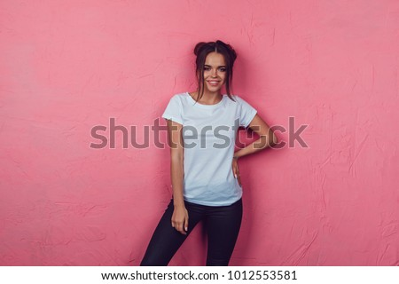 Stock Photo Attractive woman in a white t-shirt stands on a pink background. Mock-up.