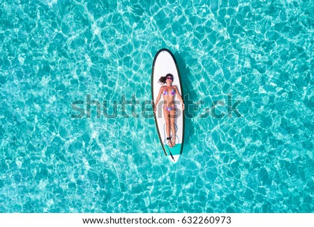 Attractive woman in bikini is sunbathing on a surfboard, aerial view