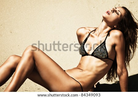attractive woman in bikini, outdoor shot in sand, summer day