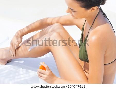 Attractive Woman In Bikini Sitting At Beach With Sun Protection Cream