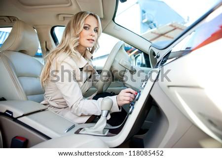 attractive woman in car driver seat adjusting radio