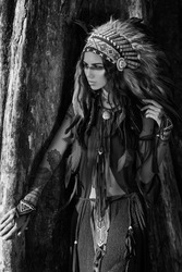 Attractive woman in chieftait outdoors. Native american style