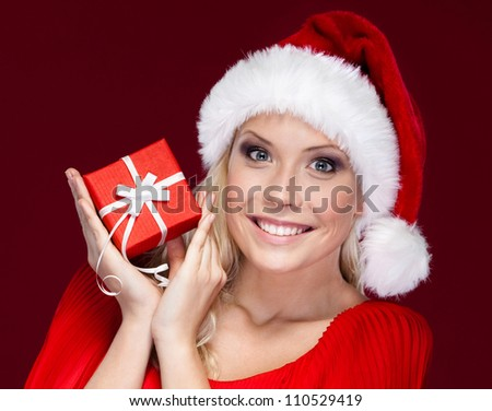 Attractive woman in Christmas cap hands a present, isolated on purple
