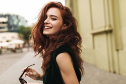 Attractive woman in dark green outfit smiling outside