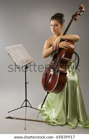Attractive woman in evening dress with cello