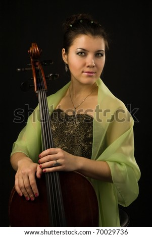Attractive woman in evening dress with cello over black