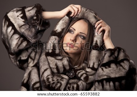 Attractive woman in fur sheepskin jacket with hood - stock photo