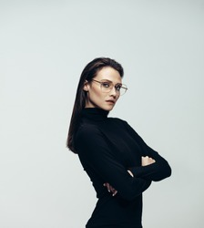 Attractive woman in glasses wearing black dress standing with her arms crossed on grey background. Confident female model in casuals.