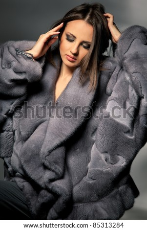 Attractive woman in gray lady's fur coat patting her hair over gray background