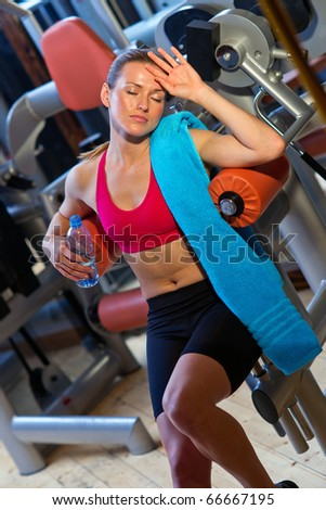 attractive woman in gym on workout machine with water bottle