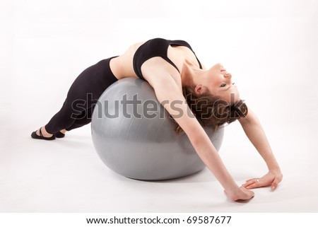 Attractive woman in gym outfit exercising with a ball