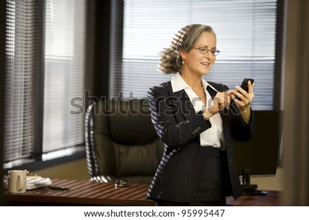Attractive woman in office using cellphone.