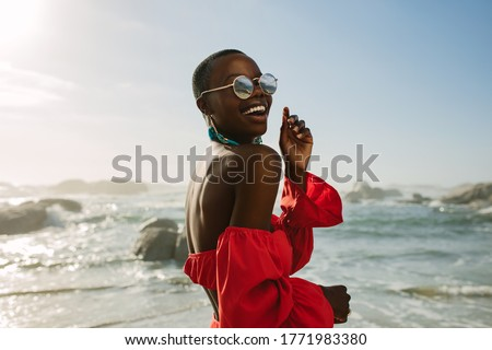 Attractive woman in red dress dancing on the beach. African woman wearing red sundress and sunglasses having fun on the beach.