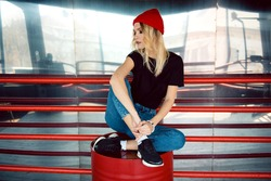 Attractive woman in red hat, black t-shirt, blue jeans and black sneakers sitting with crossed legs on barrel. Concept of people, hipster and lifestyle.