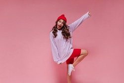 Attractive woman in red hat, cycling shorts and purple hoodie moves on pink background. Curly girl rises leg on isolated backdrop.