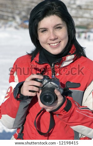 Attractive woman in sport wear holding a camera, winter outdoors (series sport, mountains, extreme, horses, teenagers)