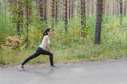 Attractive woman in sports clothes doing sports exercises on the road, loves gymnastics, stretching her legs. An active young girl is engaged in sports, leads a healthy lifestyle in the Park outdoors.
