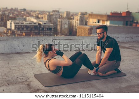 Attractive woman in sportswear doing sit ups on a building rooftop terrace with the assistance of a personal fitness instructor. Focus on the instructor #1115115404