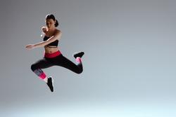 attractive woman in sportswear jumping on grey