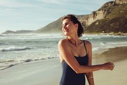 Attractive woman in swimwear on the beach on a summer day. Female in swimwear walking on the beach.