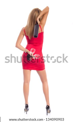 Attractive woman in tight red dress turned away from the camera holding a bottle of wine and two glasses