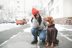 Attractive woman in warm clothes sitting on the street with a dog looking at a pet and smiling against the backdrop of winter streets and buildings. Winter walk with a dog in doggy clothes.