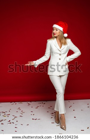 attractive woman in white suit with a red and white hat on her head doen't smiles Stockfoto ©
