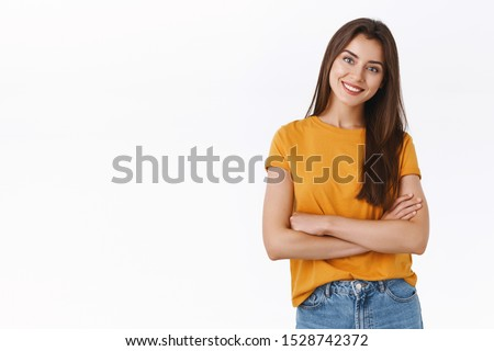 Attractive woman in yellow t-shirt cross hands over chest with self-assured, pleased expression, tilt head and smiling satisfied, look at good result, cheering and expressing positive emotions #1528742372