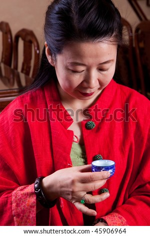 Attractive woman inside a traditional tea house, reading her tea leaves