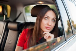 Attractive woman is enjoying her journey. She is sitting on back seat in car and smiling. The lady is looking through the window and dreaming