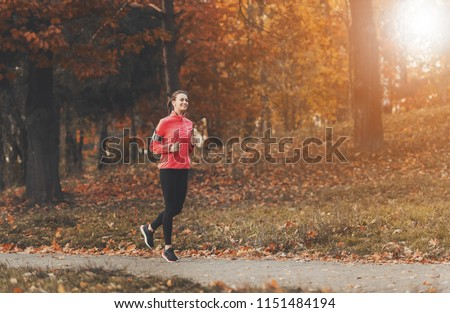 Attractive Woman Jogging. Autumn Outdoor. Female Runner in Park. Fitness and Wellness Concept. Healthy Lifestyle. Young Beautiful Woman. Sport Lifestyle. Listening Music Composition. #1151484194