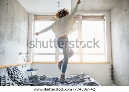 attractive woman jumping on bed in the morning, curly hair, casual style, blue jeans, white sweater, happy, natural window light