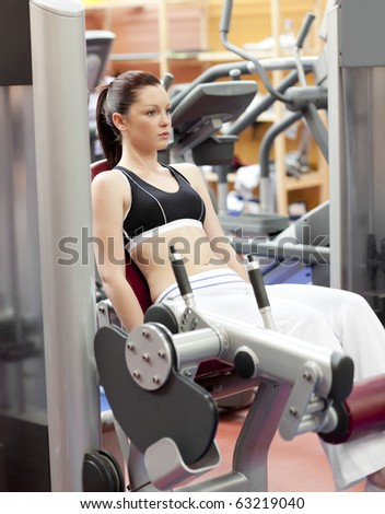 Attractive woman lifting weights with a leg press in the room of a sport centre